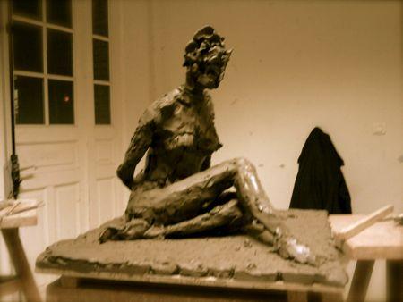 Femme aux jambes croisées au sol sculptée d'après ronde-bosse